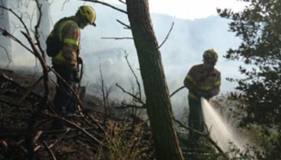 Dos bombers apagant un dels focs d'Alforja.