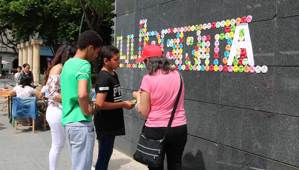 Un grup de reusencs escriu el nom 'Llibertat' amb flors d'origami. Imatge del 27 de maig de 2017