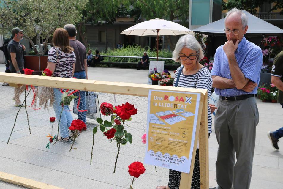 Una parella mira les flors penjades, amb un cartell que anuncia l'acció en primer pla. Imatge del 27 de maig de 2017