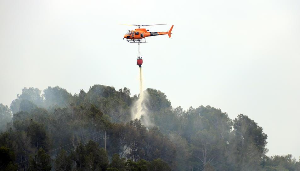 Pla tancat d'un helicòpter dels Bombers descarregant aigua en un incendi que s'ha originat a Picamoixons, a l'Alt Camp, el 30 de maig del 2017