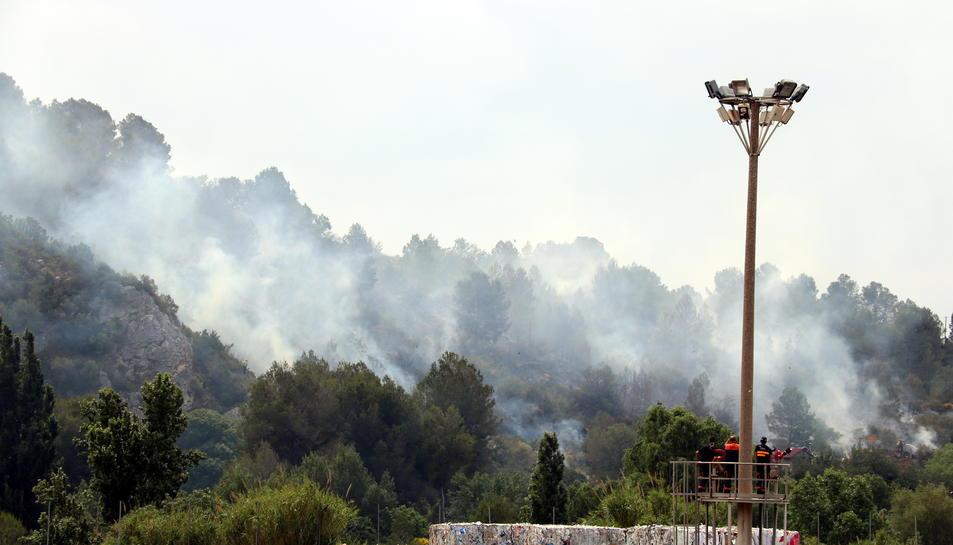 Pla general d'uns treballadors de la paperera d'Alcover, observant la fumera d'un incendi a Picamoixons (Alt Camp), el 30 de maig del 2017