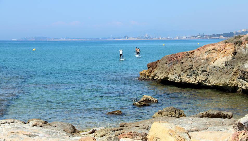 El moll romà localitzat a la platja de Roca Plana, amb uns joves practicant pàdel surf i amb la ciutat de Tarragona al fons.