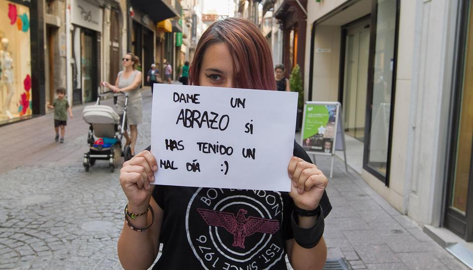 Imatge de l'Olga Mateo amb el cartell en qüestió tapant-li el rostre al carrer Monterols.