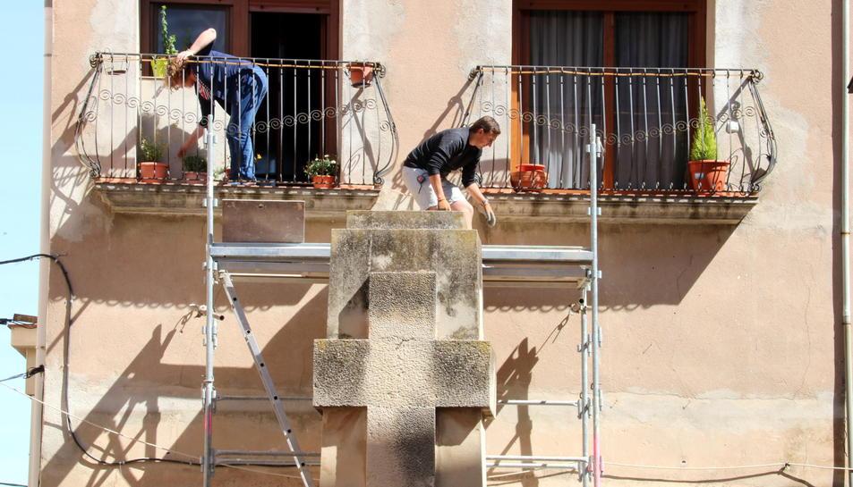 Una veïna al balcó amb les plantes mentre un operari preparava la retirada de la creu franquista de Vilalba dels Arcs, aquest 6 de juny de 2017