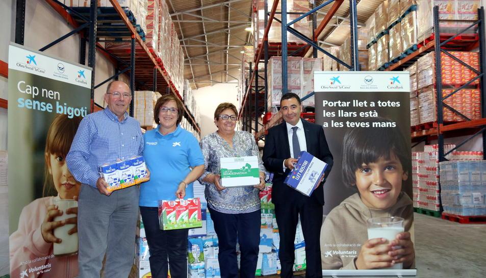Antoni Garcia, del Banc d'Aliments; Anna Miret, dels voluntaris de 'la Caixa'; Mª Luz San Miguel, representant de l'entitat benèfica; i Jordi Creus, director d'una oficina de CaixaBank, a la seu de l'entitat a Reus, el 6 de juny del 2017