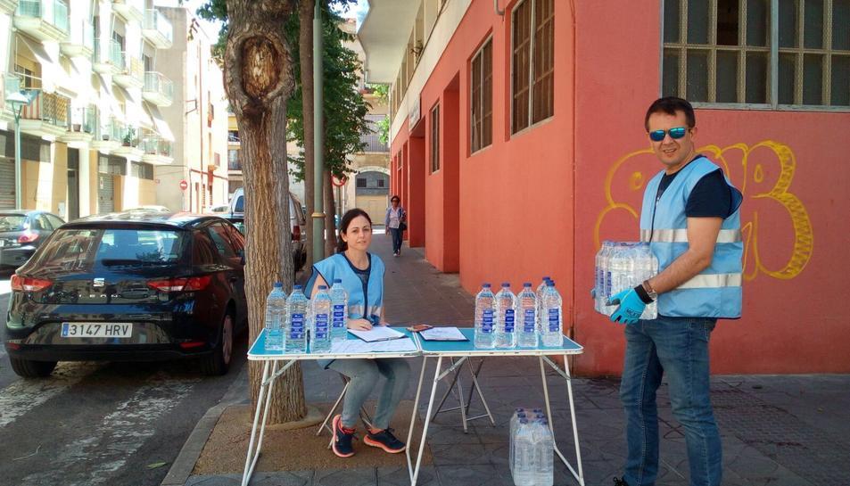 Imatge del punt de repartiment d'ampolles d'aigua pels veïns.