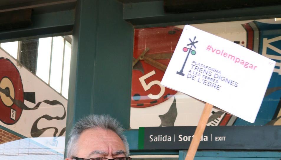Pla americà del representant de la plataforma Trens Dignes, Josep Casadó, mostrant el seu bitllet d'Euromed per al viatge reivindicatiu amb una pancarta amb el lema