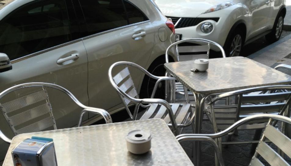 Les taules i les cadires de la terrassa estan tocant els vehicles estacionats.