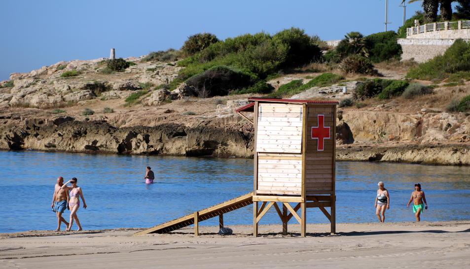Una torre d'intervenció immediata de la Creu Roja a la platja de l'Arrabassada de Tarragona, i banyistes passejant i banyant-se al mar, el 13 de juny del 2017