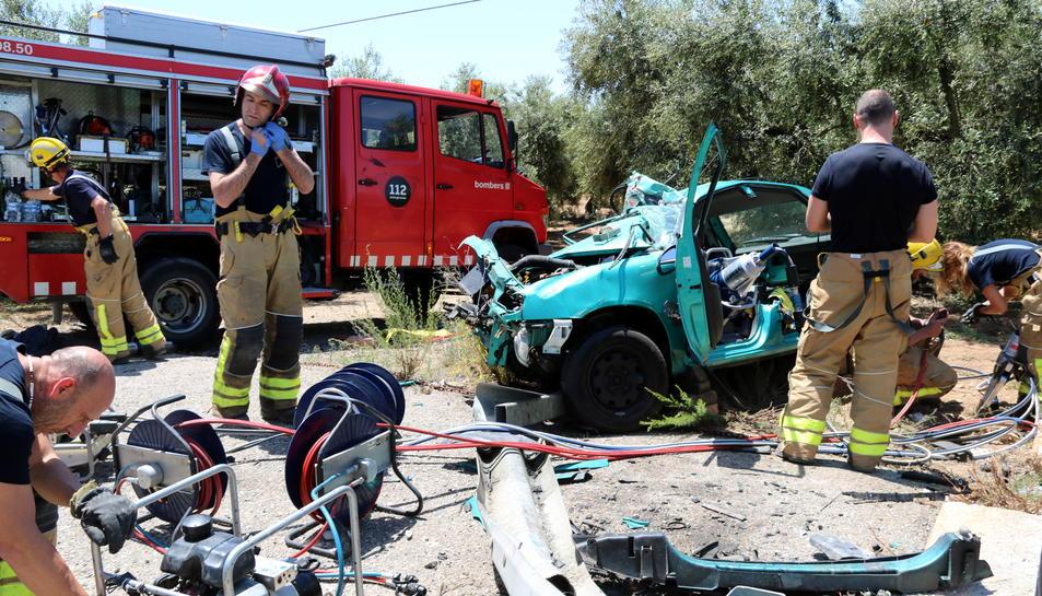 Pla obert de diversos Bombers al costat del vehicle accidentat a la T-302 a Cambrils. Imatge del 14 de juny del 2017
