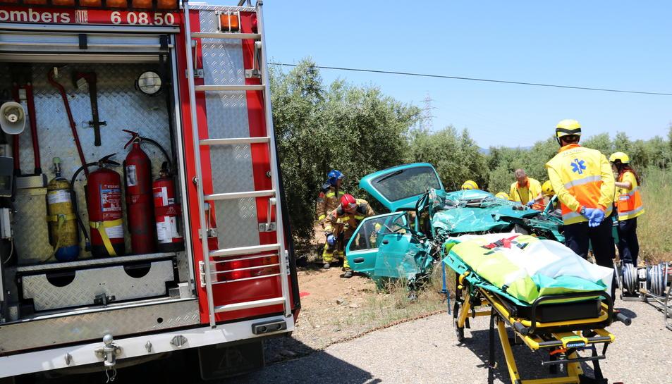 Pla obert del punt de la T-302 on un vehicle ha partit una sortida de via i dels sanitaris atenent la conductora, que ha quedat atrapada. Imatge del 14 de juny del 2017