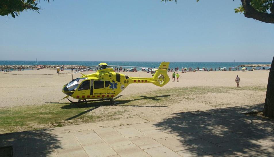 Pla obert de la platja de l'Horta de Santa Maria de Cambrils amb l'helicòpter a la sorra en primer pla. Imatge del 17 de juny de 2017