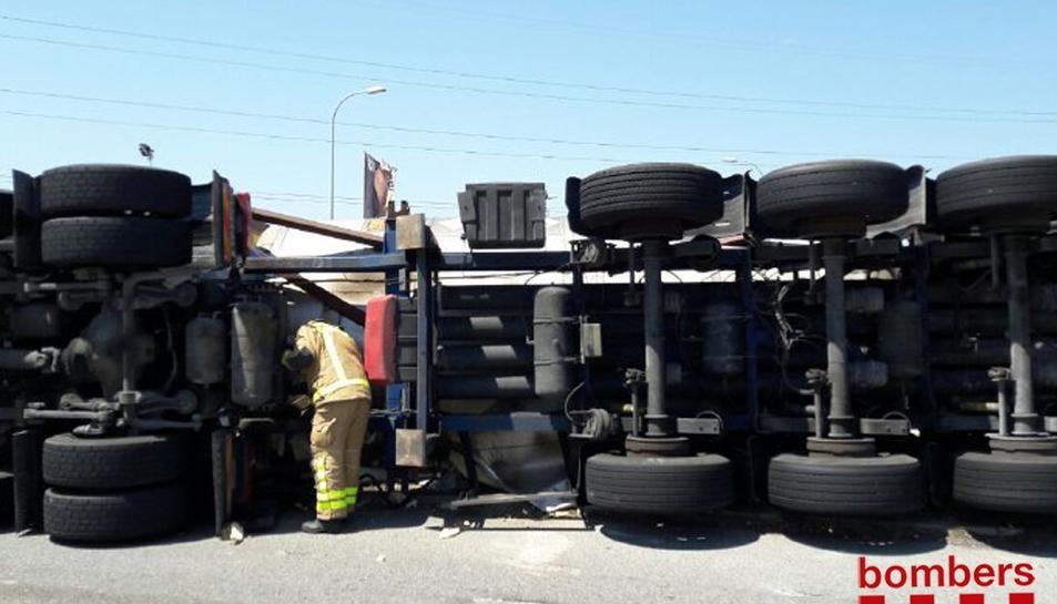 El camió ha quedat bolcat enmig de la via.