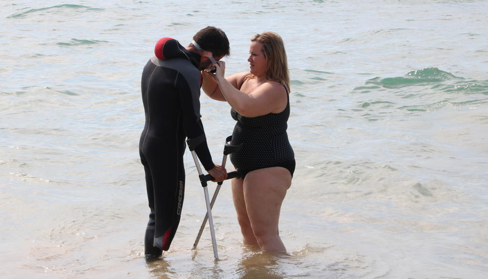 Una dona posa les ulleres de busseig a un participant que va amb crosses, dins a l'aigua. Imatge del 23 de juny de 2017