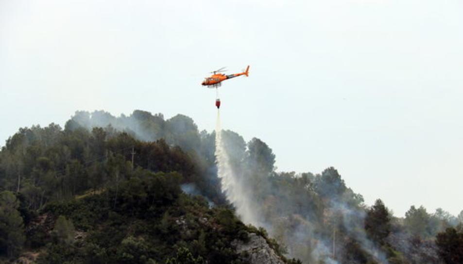 Pla general d'un helicòpter dels Bombers descarregant aigua en un incendi que s'ha originat a Picamoixons, a l'Alt Camp, el 30 de maig del 2017.