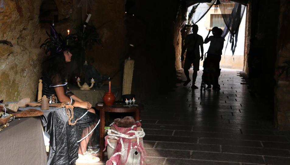 Pla obert d'una bruixa, a la dreta, i dos visitants entrant al passatge. Imatge del 25 de juny de 2017