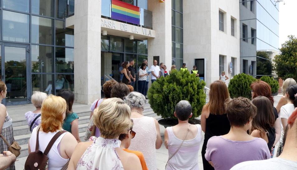 Pla general de diverses persones concentrades davant l'Ajuntament de Cambrils per condemnar la mort d'una dona a mans de la seva exparella, amb l'alcaldessa, al fons, llegint un manifest. Imatge del 26 de juny del 2017