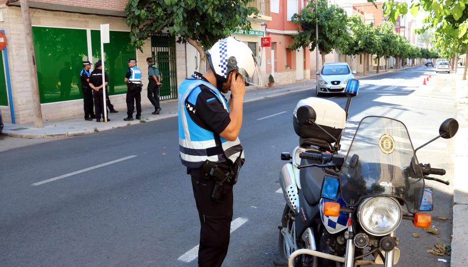 Un agent de la Policia Local d'Amposta amb la seva moto en primer pla amb altres agents al fons custodiant el registre d'un club cannàbic d'Amposta en el marc d'una operació antidroga al Montsià. Imatge del 238 de juny de 2017 (horitzontal)