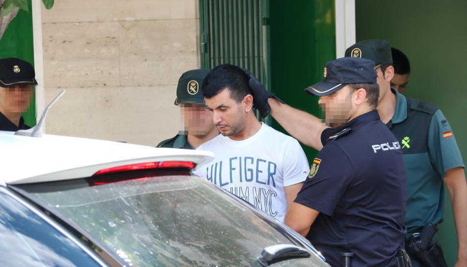 Agents de la Policia Nacional i la Guàrdia Civil s'enduen detingut el propietari d'un club de cànnabis d'Amposta i el fan pujar al cotxe policial. Imatge del 28 de juny de 2017 (horitzontal)