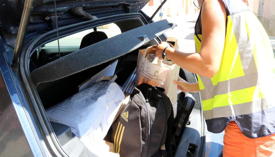 Una agent guarda al maleter d'un cotxe policial una bossa amb marihuana que han confiscat a l'associació cannàbica d'Amposta, en l'operació contra el tràfic de drogues al Montsià. Imatge del 28 de juny de 2017 (horitzontal)