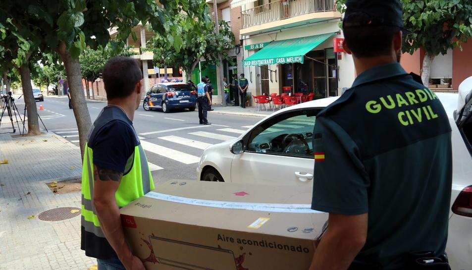 Pla americà de sos agents de la Policia Nacional i la Guàrdia Civil  transportant en una caixa de cartró material intervingut en l'operació antidroga que han dut a terme en diverses poblacions del Montsià. Imatge del 28 de juny de 2017 (horitzontal)