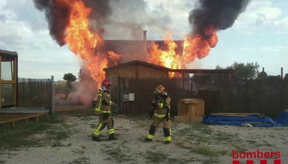 Imatge dels bombers treballant en l'extinció del foc que ha cremat una casa de fusta a Reus.