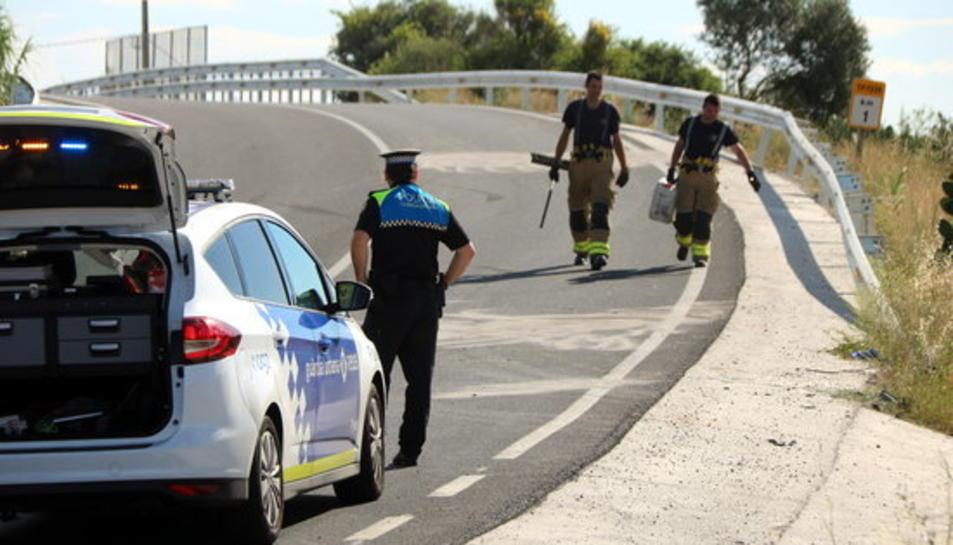 Pla general del punt de l'accident a la TP-7225 a Reus, amb un vehicle de la Guàrdia Urbana en primer terme i dos bombers al fons.