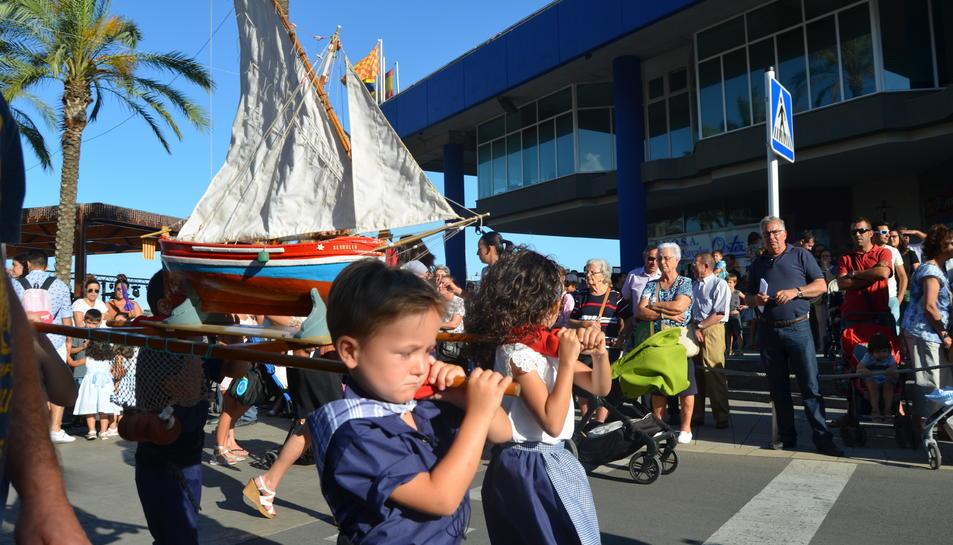 Uns nens vestits de pescadors porten un vaixell a espatlles.