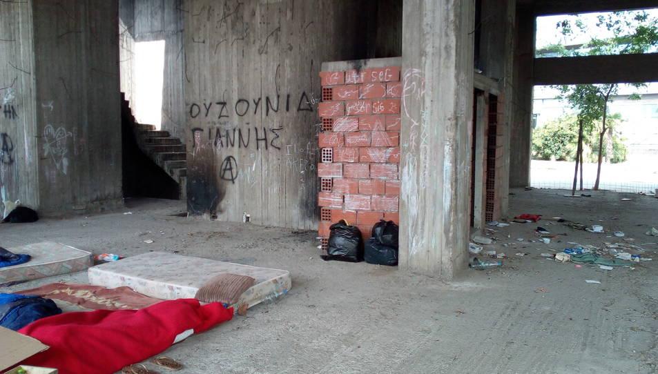 Detall d'un matalàs a terra amb mantes i un coixí.