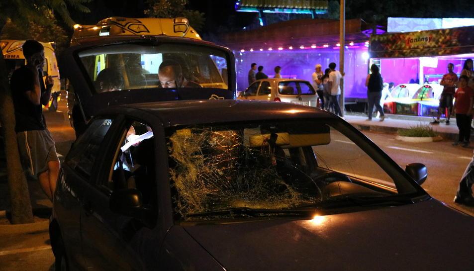Primer pla del cotxe implicat en l'atropellament davant de la zona d'atraccions ambulants de la festa major de Roquetes, amb alguns agents dels Mossos d'Esquadra treballant a la part posterior. Imatge del 2 de juliol de 2017 (horitzontal)