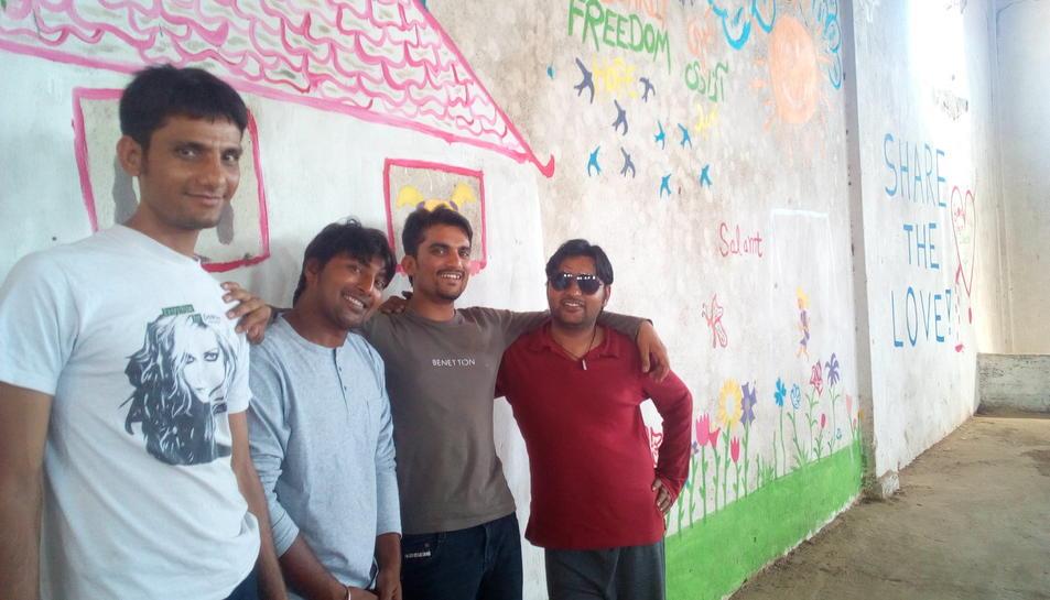 El Salamt, l'Ali, el Zaheer i l'Amjad somriuen al davant de la pintura que van elaborar junt amb els voluntaris.