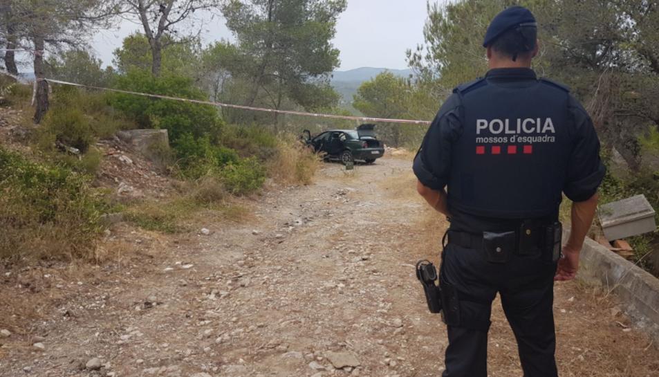 Un agent de Mossos d'Esquadra, amb el cotxe del detingut al fons.