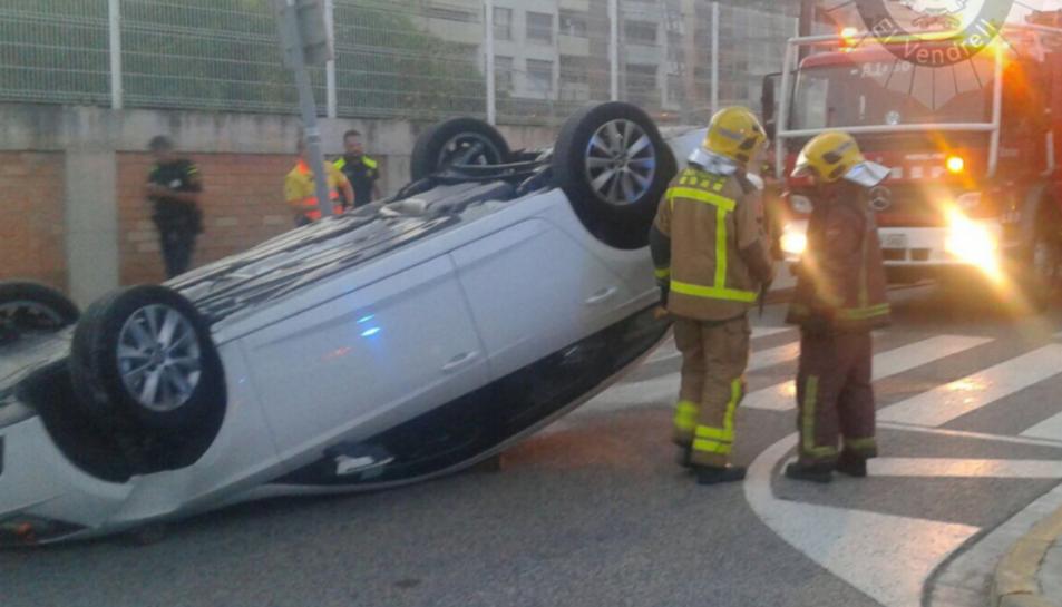 El cotxe va quedar totalment bolcat al mig del carrer.