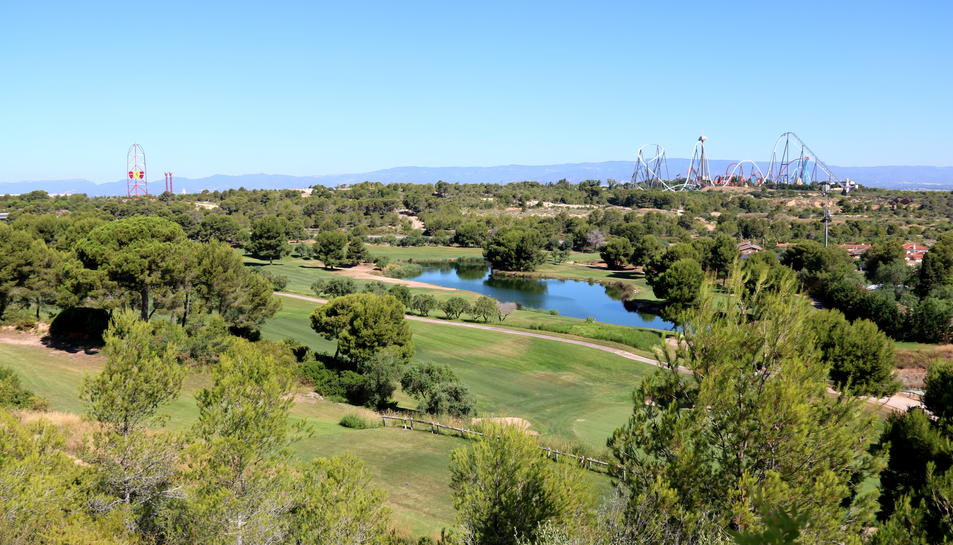 Panoràmica dels terrenys on s'ha projectat el Centre Recreatiu i Turístic (CRT) de Vila-seca i Salou, amb el parc temàtic PortAventura, de fons, en una imatge del juliol del 2017