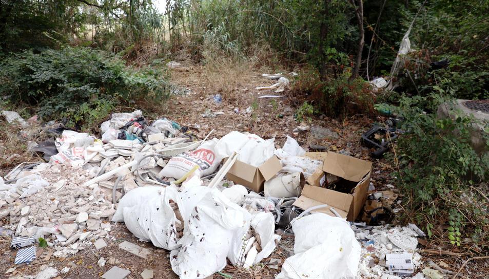 A la imatge, restes del material d'obra que s'acumula a un camí que s'endinsa a la llera del riu.