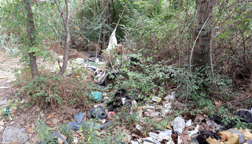 A la imatge, brutícia acumulada a l'altra banda del camí, amb restes d'electrodomèstics al fons.