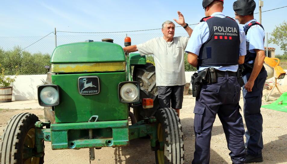 Pla general de dos agents dels Mossos d'Esquadra conversant amb un pagès al costat del seu tractor en un mas de Vallmoll (Alt Camp), el 7 de juliol del 2017
