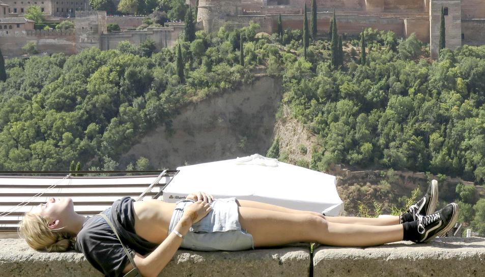Una turista prenen el sol a la ciutat de Granada.