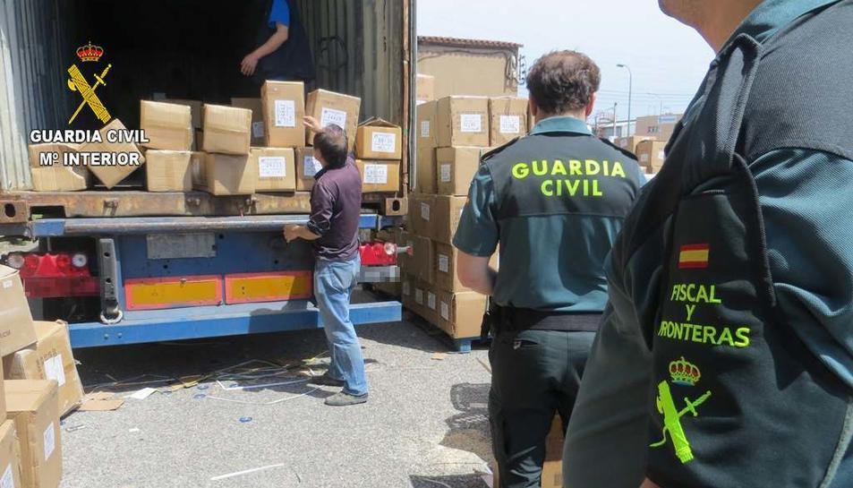 Imatge de la Guàrdia Civil descarregant el material incautat del camió.