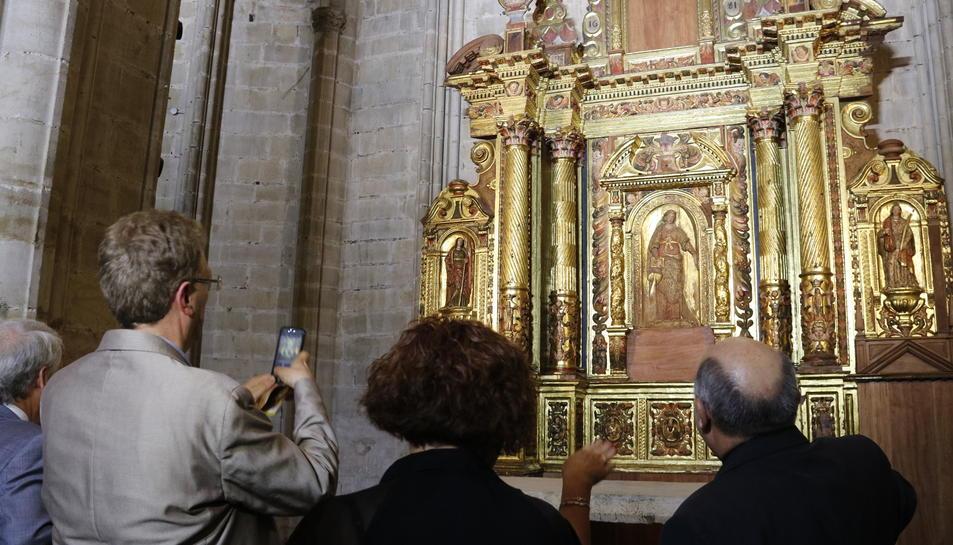 Pla mig del retaule barroc amb l'alcalde de Tortosa, Ferran Bel, d'esquena, fent una foto amb el mòbil, i el bisbe de Tortosa, Enric Benavent, d'esquena, explicant les particularitats de la peça d'art, aquest 13 de juliol de 2017
