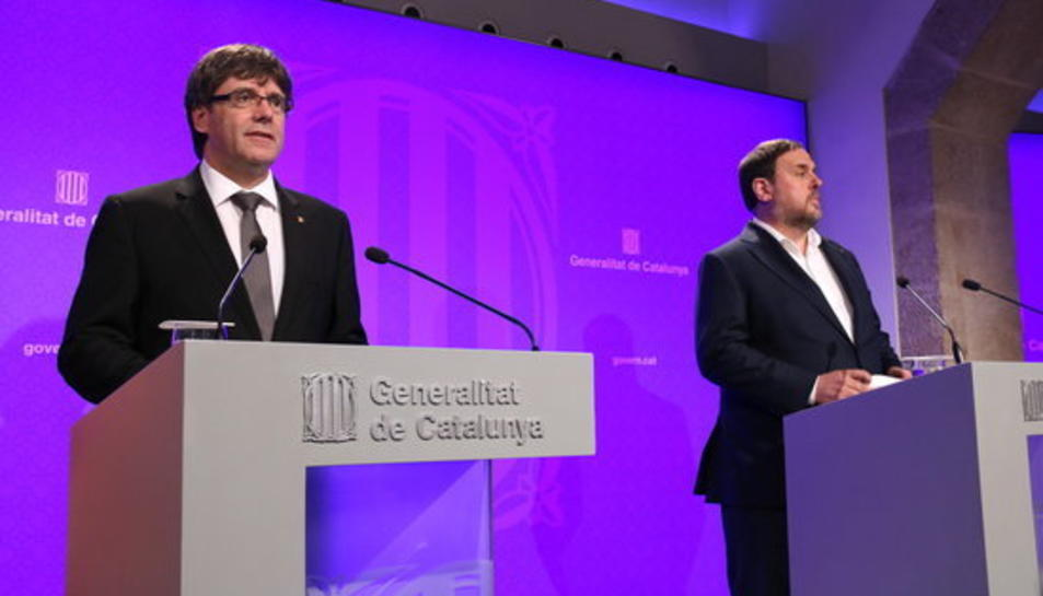 El president del Govern, Carles Puigdemont, i el vicepresident, Oriol Junqueras, compareixen a la sala de premsa del Palau de la Generalitat per explicar els canvis a l'executiu.