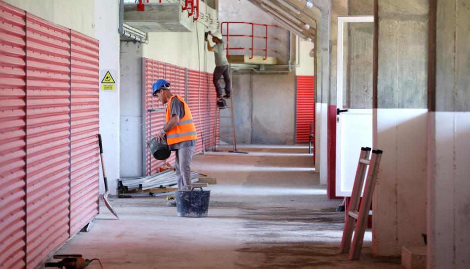 Dos treballadors, a la zona de Tribuna, realitzant els treballs previs a l'acabat de la zona.