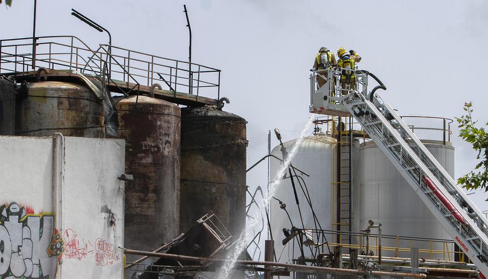 Els Bombers remullant els dipòsits de fibres que s'han incendiat.