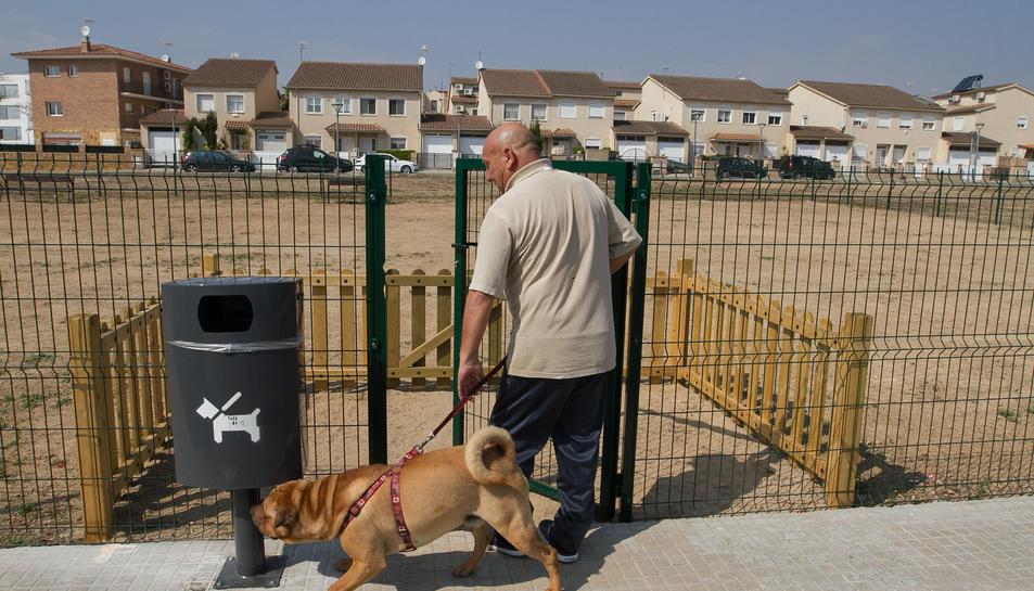 Un home passeja el seu gos en un pipican instal·lat al barri Juroca de Reus.