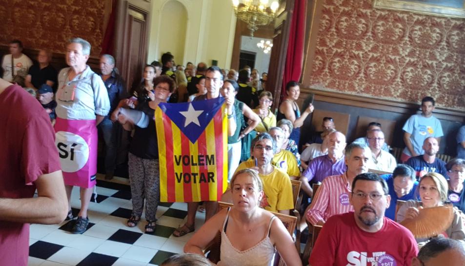 Imatge d'assistents al ple amb banderes en què s'hi pot llegir 'sí' i 'volem votar'.