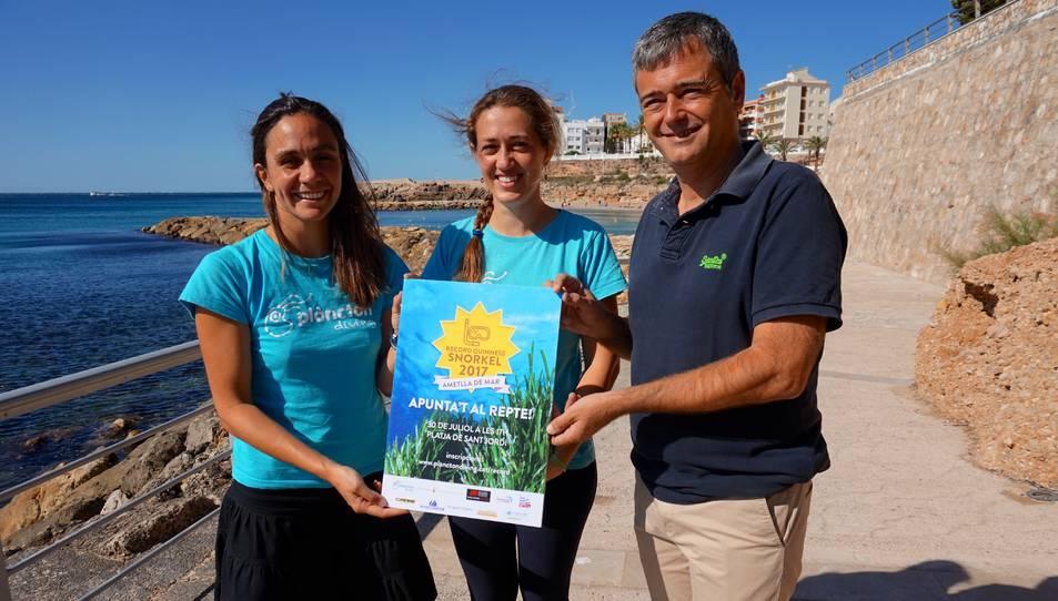 Les copropietàries de l'empresa organitzadora, Plàncton Diving, i l'alcalde de l'Ametlla de Mar, amb el cartell de l'esdeveniment.