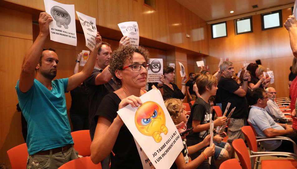 Un grup de treballadors mostrant cartells de rebuig per l'aprovació de l'augment salarial.