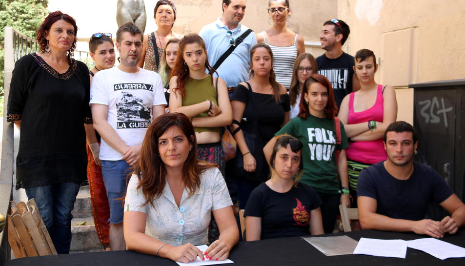 Foto de grup de regidors i simpatitzants de la CUP de Reus a les escales de les Peixateries Velles, en una roda de premsa per denunciar un suposat cas de violència masclista i qüestionar l'actuació policial. Imatge del 26 de juliol del 2017