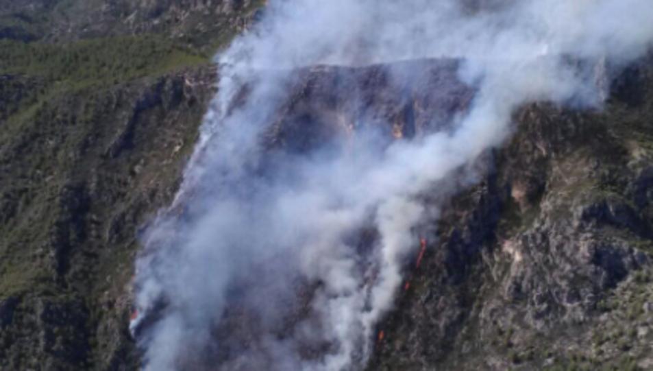 Imatge aèria de l'incendi, que ha començat al fons d'un barranc i ha arribat al capdamunt de la serra.