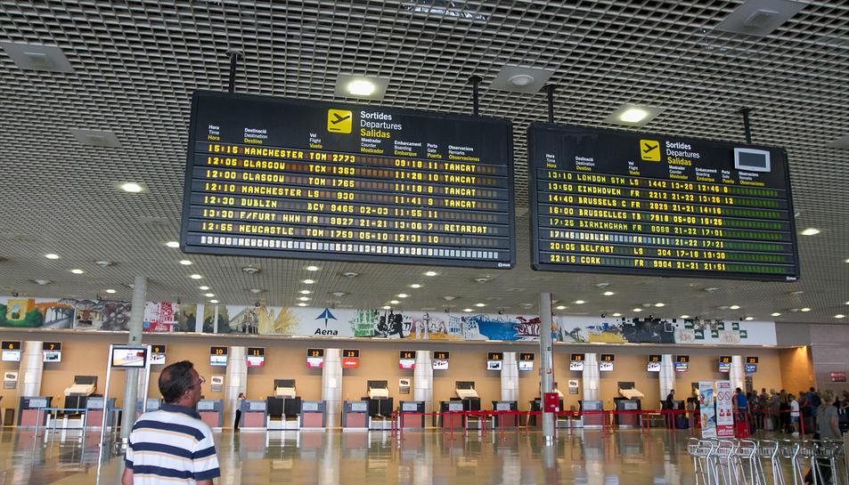 Un usuari consulta les pantalles informatives a l'aeroport de Reus.